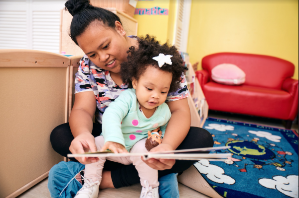 Child care provider reading a book with toddler